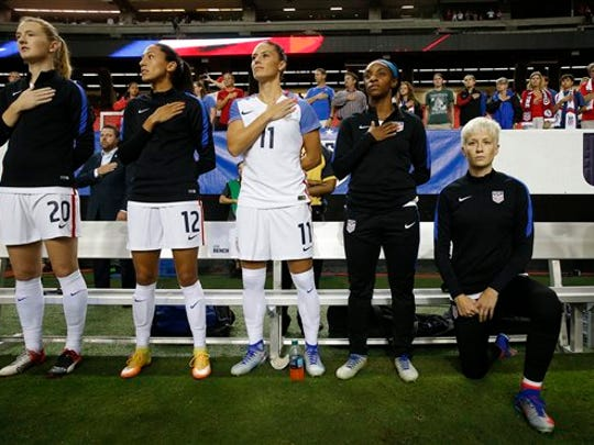 USA's Megan Rapinoe, right, kneels next to teammates
