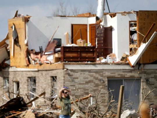 A woman walks past a destroyed home in the aftermath of Tuesday's tornado that tore through the New Orleans East section of New Orleans, Wednesday, Feb. 8, 2017.  Officials say tornadoes that struck in southeastern Louisiana destroyed homes and businesses, flipped vehicles and left thousands without power.