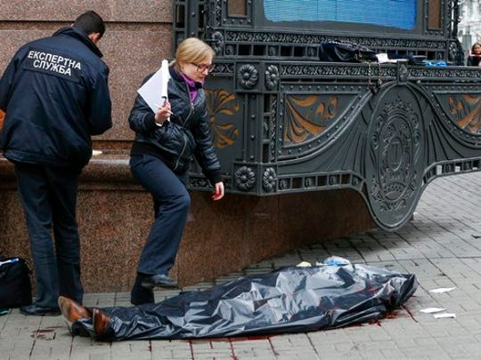 Forensic experts and police officers work at the scene following the killing of Denis Voronenkov in Kiev, Ukraine, Thursday, March 23, 2017. Ukrainian police said Voronenkov was shot dead Thursday by an unidentified gunman at the entrance of an upscale hotel in the Ukrainian capital. Voronenkov, 45, a former member of the communist faction in the lower house of Russian parliament, had moved to Ukraine last fall and had been granted Ukrainian citizenship.