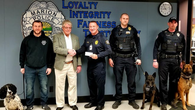 Don Byrnes shakes hands with Marion Police Chief Bill Collins surrounded by the department's K-9 unit.
