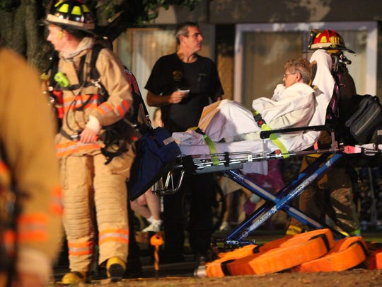 Covington firefighters take a woman who was injured in a fire to the hospital from Hathaway Court senior apartments Monday night.