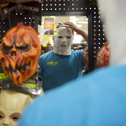 Kane Covington tries on a mask at the Spirit Halloween