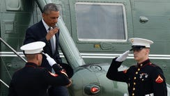 President Obama returns a salute as he walks off of