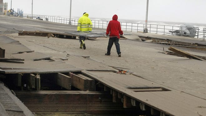 Residents examine damage to the boardwalk in Belmar, N.J., after Superstorm Sandy.