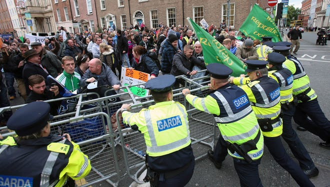 Police hold a line of barriers as protestors gather outside the government in Dublin, as politicians return after the summer recess on Wednesday.