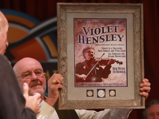 Violet Hensley celebrated her 100th birthday at Silver Dollar City on Friday,where she has demonstrated her fiddle making craft for 50 years. She was born on Oct. 21, 1916. Pete Herschend holds a plaque that will be displayed in the gazebo honoring Hensley.