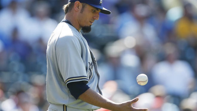 Milwaukee Brewers starting pitcher Matt Garza reacts after giving up a double to Colorado Rockies' Charlie Blackmon that brought in two runs in the sixth inning of a baseball game Sunday in Denver.