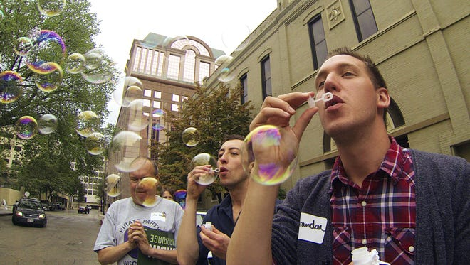 Brandon Herr, right, and Matt Antonczyk blow bubbles at a rally Monday, Aug. 25, 2014 in Milwaukee as gay couples and their supporters board a bus for a trip to Chicago for a key hearing in the fight against same-sex marriage bans. On Tuesday the 7th Circuit Court of Appeals in Chicago will hear oral arguments in a combined appeal from Wisconsin and Indiana where same-sex marriage were ruled unconstitutional in June.