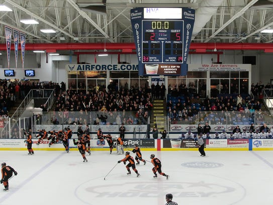 Brighton hockey players spill onto the ice to celebrate