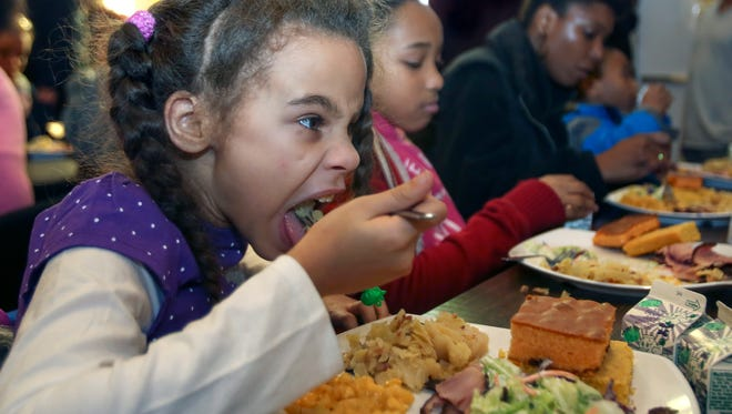 Kiana Cole enjoys the lunch and music at St. Vincent de Paul's Open Hand Kitchen. Cole is a part of the Family Success Center, an after school program for at risk kids. Dec. 19, 2015