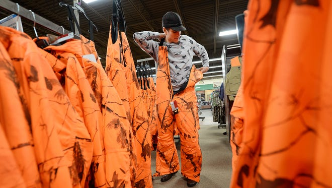 Tyler French of Suring tries on blaze orange thermal overalls at Gander Mountain in Howard on Nov. 20, 2014.