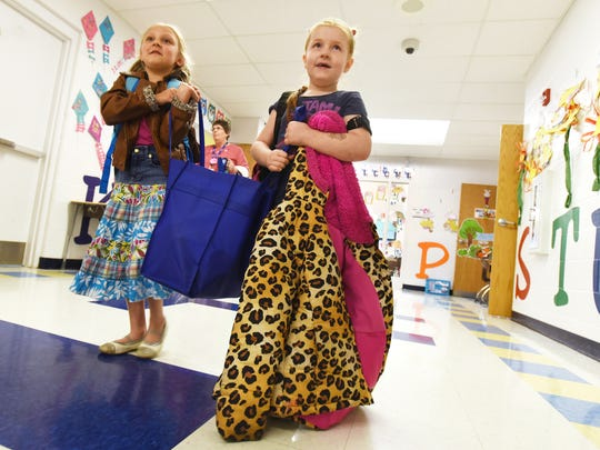 Claire Lyons, right, gets a helping hand from her friend Payton Phillips as she carries her bag of food down the hall at Zane Grey Elementary School on Tuesday. The Zanesville Noon Rotary donated bags of food so students would have something to eat during the upcoming spring break.