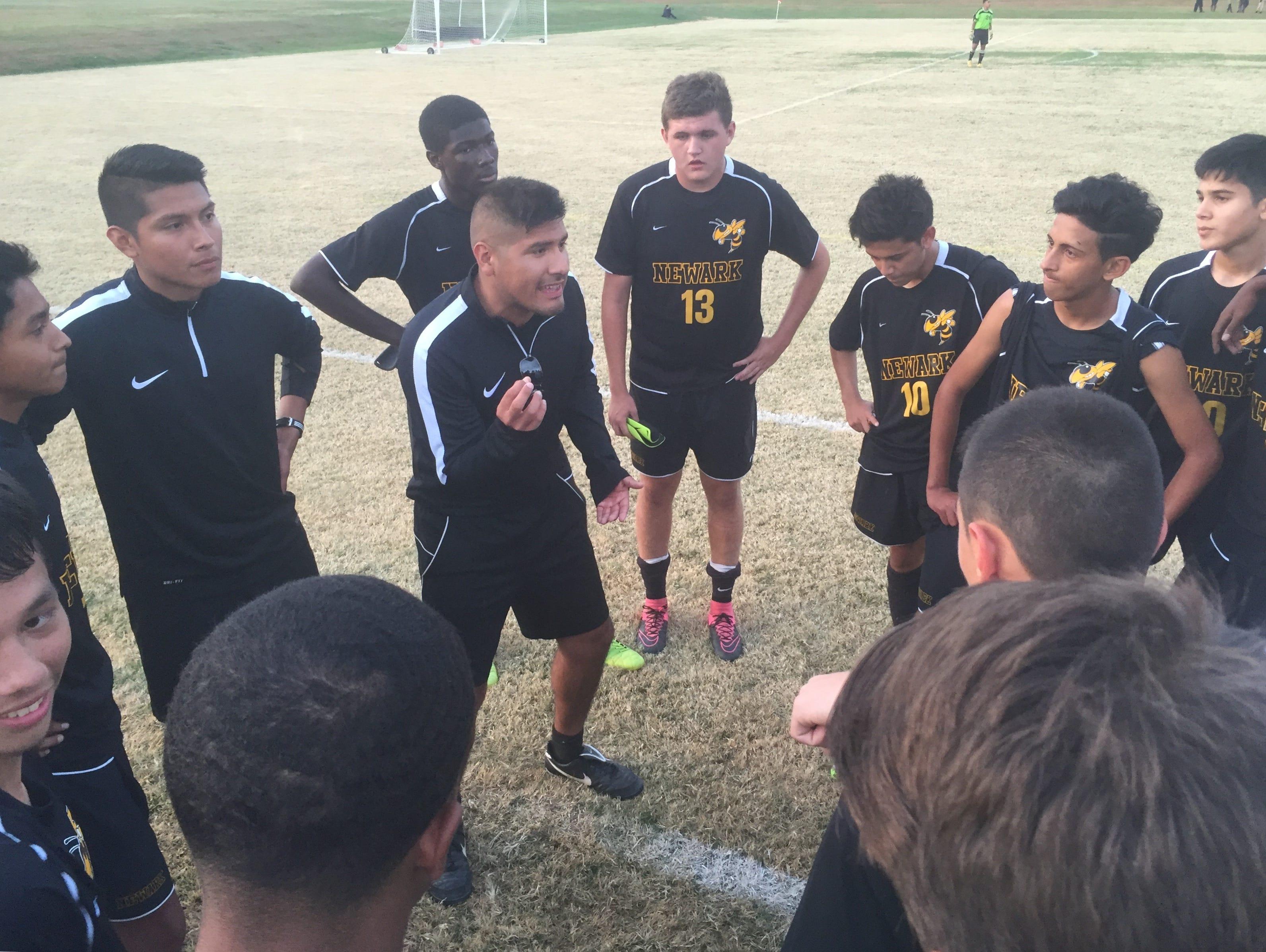 Newark boys soccer coach Diego Ruiz congratulates his team after a 2-1, double-overtime win at Delcastle on Thursday.