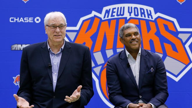 Knicks president Phil Jackson, left, and general manager Steve Mills answer questions during a news conference at the team's training facility, Jackson said that today's NBA players often don't have the skills to play the triangle offense.