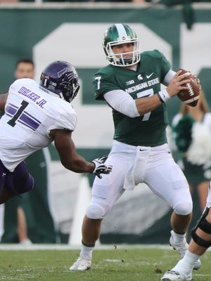 Michigan State Spartans quarterback Tyler O'Connor is pressured by Northwestern's Anthony Walker during the second half Saturday, Oct. 15, 2016 at Spartan Stadium.