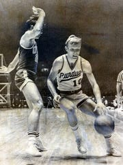 Rick Mount of Purdue drives the sideline against UCLA's Kenny Heitz in the first half of the NCAA finals at Louisville's Freedom Hall.