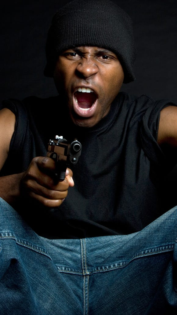 This is a photo illustration of a black man in gang-type apparel with gun.