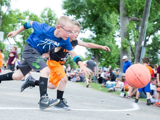 Emmitt Anderson, 7, blue, chases a basketball during