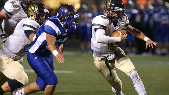 Decatur Central High School quarterback Tommy Stevens runs 24 yards on a broken play for the game's first touchdown at 7:33 in the first quarter against the Franklin Grizzly Cubs in Franklin on Friday, October 17, 2014. At halftime, the Hawks hold a 14-13 lead over the Grizzly Cubs.