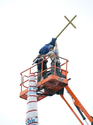 Workers set the cross atop the spire of the new Hermance Family Chapel of St. Basil the Great at St. John Fisher College.