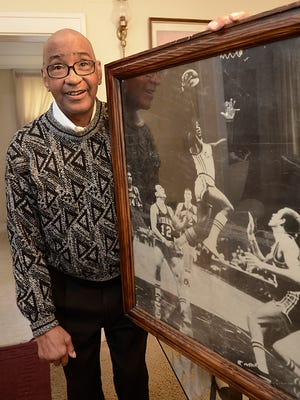 Basketball legend Henry Logan, shown in 2014, with a photo of him playing in 1968 with the Oakland Oaks of the ABA