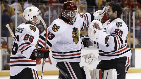 Chicago Blackhawks goalie Scott Darling (33) celebrates with goalie Corey Crawford (50) and left wing Teuvo Teravainen (86), of Finland, after the Blackhawks defeated the Nashville Predators 4-3 in two overtimes in Game 1 of an NHL Western Conference hockey playoff series Wednesday, April 15, 2015, in Nashville, Tenn. (AP Photo/Mark Humphrey)