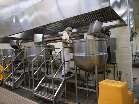 An inmate at James T. Vaughn Correctional Center prepares a large pot of soup in the prison kitchen.