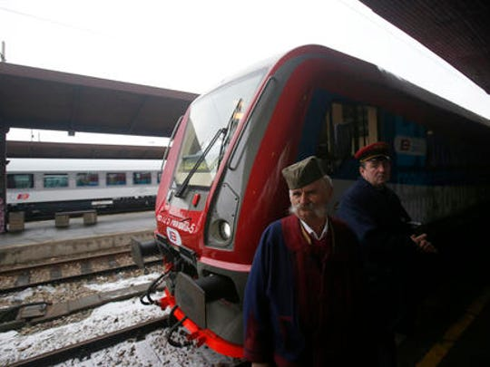 "A man dressed in Serbian national costume passes by a train decorated with ""Kosovo is Serbian"" inscribed in twenty world languages before it departs from Belgrade to Mitrovica, Kosovo at Belgrade's railway station, Serbia, Saturday, Jan. 14, 2017. Serbia has launched a railway link to Serb-dominated northern Kosovo despite protests from authorities in Pristina who described the move as a provocation and an aggressive violation of Kosovo's sovereignty."