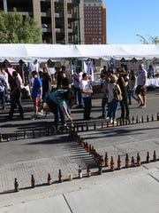 Festival-goers create a giant beer bottle out of used