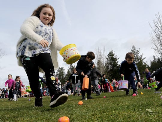 Jasmine Brookes, 7, (left) makes a dash for some eggs during the mEGGa Hunt at Bainbridge Island's Battle Point Park on Saturday, March 31, 2018.