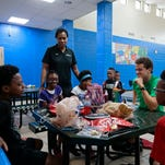 Girls take a look at Jamelle Elliott's six national championship rings at the Girls and Boys Club in the Avondale neighborhood of Cincinnati on Friday, July 1, 2016. Elliott has won national titles as a player and assistant coach at the University of Connecticut, and told the girls about meeting four United States presidents as a reward.