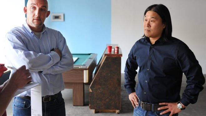 CHRISTOPHER WALKER/TIMES RECORD NEWS Beau Dameron (left) and Sam Pak talk Friday afternoon after closing the purchase at 922 Indiana Ave. downtown.