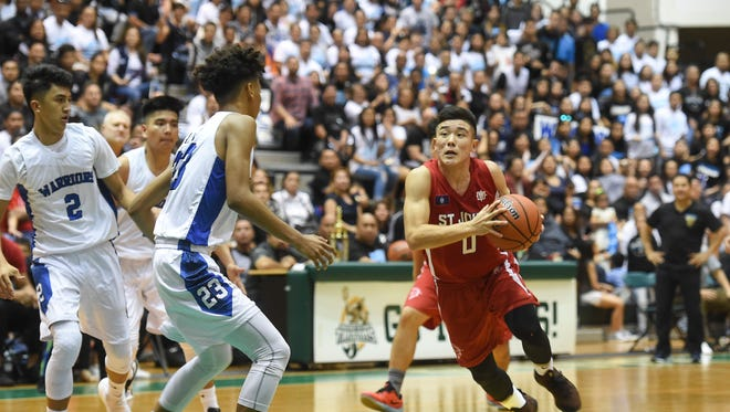In this file photo, St. John's Michael Min drives to the basket during the IIAAG High School Boys' Basketball Championship game at the University of Guam Calvo Field House on March 9, 2018.