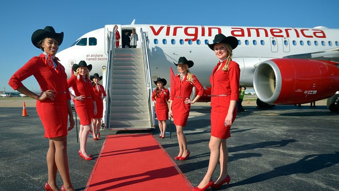 Virgin America flight attendants line the red carpet during a news conference at Dallas Love Field on April 25, 2014.