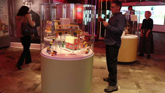David DuBois, a member of the Little People team at Fisher-Price, takes a photo of the Little People display at the National Toy Hall of Fame on Thursday, Nov. 10, 2016.