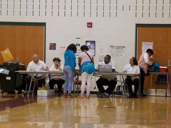Voting poll workers help voters for the primary election