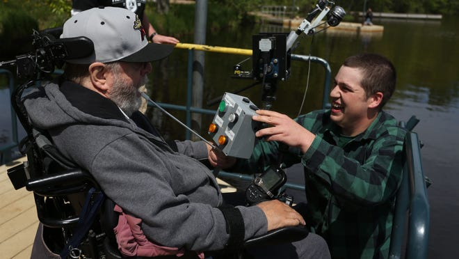 Thor Gunderson, right, a recently graduated NTC student. reacts after Jim DeBroux of Mosinee successfully made a cast at River Park in Mosinee, Wednesday, May 20, 2015, with the adaptive fishing pole that Gunderson helped design and build as part of his work in the electromechanical technology program at NTC. DeBroux pushed a button on the controller Gunderson is holding with the control stick he holds in his mouth to initiate the cast.