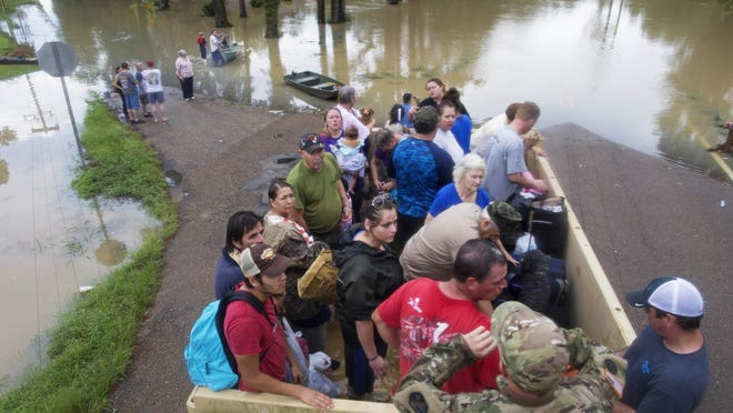 Sgt. Brad Stone of the Louisiana Army National Guard gives safety instructions to people loaded on a truck after they were stranded by rising floodwater near Walker, after heavy rains inundated the region Sunday.