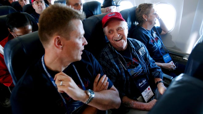 Andrew Johnston, 88, of Boynton Beach, shown with volunteer guardian Mitchell Hanson, left, of Fort Lauderdale, U.S. Air Force, and daughter Nancy O'Day, of Boynton Beach, aboard the Southeast Florida Honor Flight from West Palm Beach to Washington, D.C, Saturday, Sept. 7, 2013. Seventy-three WWII veterans and volunteer guardians from Palm Beach County and the Treasure Coast on an Honor Flight, a whirlwind, one-day trip from South Florida to the WWII Memorial, Vietnam Memorial, Arlington National Cemetery and the Marine Corps War Memorial (also called the Iwo Jima Memorial) at the Nations Capital.