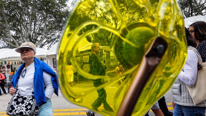 Vicky Gray (L) of Vero Beach checks out the glasswork of Stan Megdall Sunday, February 14, 2016 during the 2016 ArtiGras Festival of the Palm Beaches held in Jupiter's Abacoa Town Center.