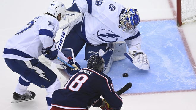Tampa Bay Lightning goaltender Andrei Vasilevskiy (88) covers the puck as defenseman Victor Hedman (77) and Columbus Blue Jackets center Pierre-Luc Dubois (18) look for a rebound during the second period of Game 3 of an NHL hockey first-round playoff series, Saturday, Aug. 15, 2020, in Toronto.