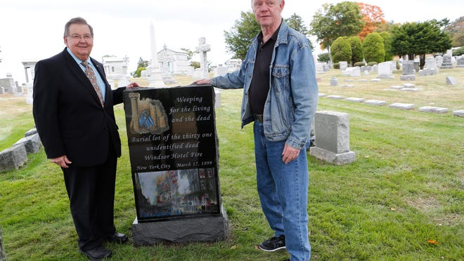 Chet Day, president of the Kensico Cemetery, and artist Al Lorenz stand Sunday next to a new monument in Kensico Cemetery dedicated to the 31 unidentified victims of the Windsor Hotel fire that took place on March 17, 1899.