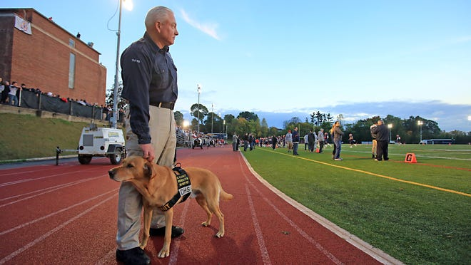 TSA agent David Wills and his explosive-sniffing dog Rriverso attend the annual Joe Riverso memorial before a football game Saturday at Stepinac High School in White Plains. Rriverso, the dog was named after the White Plains man who died in the World Trade Center on 9/11.
