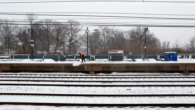 A Metro-North employee clears snow at the Pelham train station in 2014. Watch for transit updates throughout the storm.