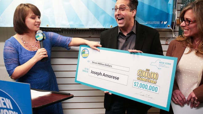 New York State Lottery draw team member Gretchen Dizer presents Joseph Amorese of Easton, Pa., and his wife, Jodi, a check for $7, 000,000 for winning the Golden Ticket drawing at the Just A Dollar store in New City on March 25, 2015.