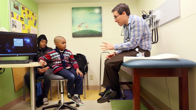 Five-year-old Aahmand Richardson listens to his pediatrician, Dr. Hal Byck, during an office visit Tuesday at Nemours' Jessup Street clinic in Wilmington. Aahmand's mother, Joy Rutland of Newark, has been taking the boy to the Nemours facility since he was born.