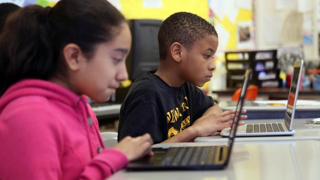 Antonia Plata, 11, and her classmate Khalif Holland, both fifth graders at Carrie Downie Elementary School research cartoons to add to the school newspaper their class was assembling in the Schoology program.