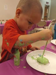 This little boy paints a rock and himself during the library's rock painting party.