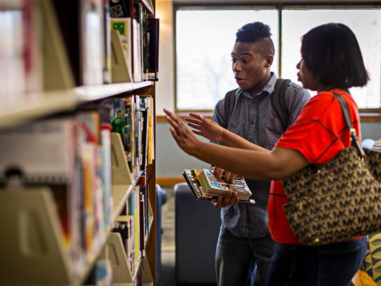 Kyan Love looks for books to check out with his mother