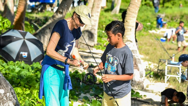 Suzanne Medina helps to bait a hook for her son, Ska Medina, 11, during the Department of Agriculture's 26th annual Saltwater Fishing Derby at the War in the Pacific National Historical Park - Asan Beach Unit on Saturday, Aug. 12, 2017.